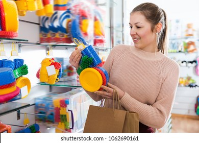 Joyful woman in the children's store assortment of plastic toys