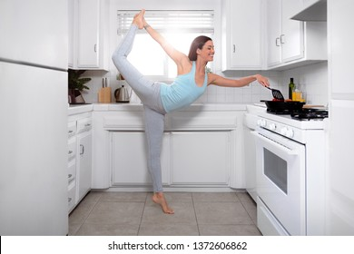 Joyful woman cooking and multitasking with yoga pose, healthy living positive attitude, wellness, wellbeing, happiness and positivity