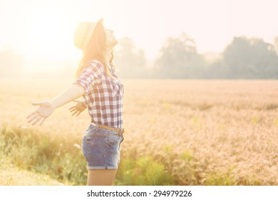 Joyful woman in the countryside with wheat field on background. She is wearing short jeans, a checked shirt and a straw hat. Freedom and happiness concepts.