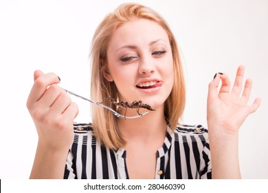 Joyful woman eating big insects with a fork in a restaurant