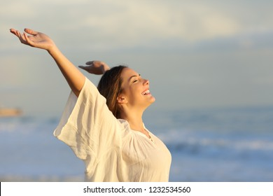 Joyful woman enjoying a day on the beach raising arms at sunset