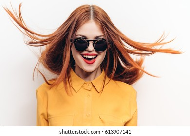 Joyful woman with flying hair in sunglasses on a light background