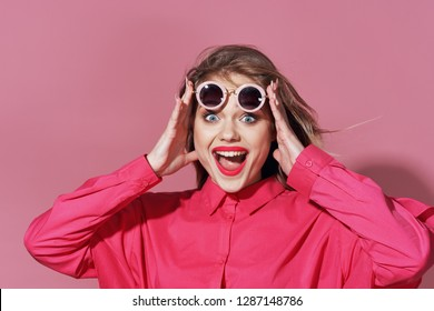 joyful woman with glasses holding her hands on her head on a pink background emotions