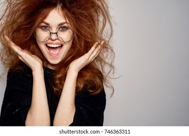 joyful woman in glasses on a light background, studio, problem with hair, emotions