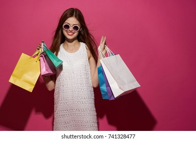joyful woman in glasses smiles on a pink background, studio, shopping