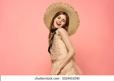 joyful woman in a hat on a pink background