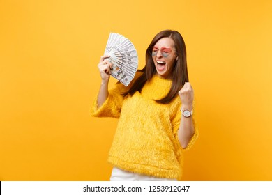Joyful woman in heart glasses screaming clenching fist like winner holding bundle lots of dollars cash money isolated on bright yellow background. People sincere emotions, lifestyle. Advertising area