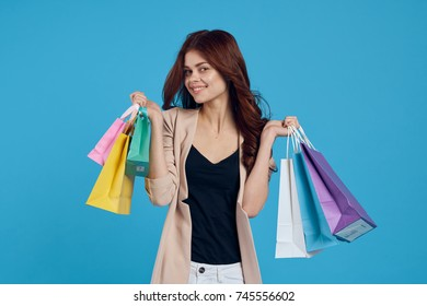 joyful woman with multi-colored packages on a blue background