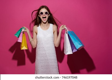 joyful woman with multicolored packages on a pink background, shopping trip
