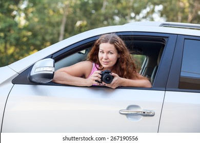 Joyful woman in pink shirt with camera in hand sitting in car