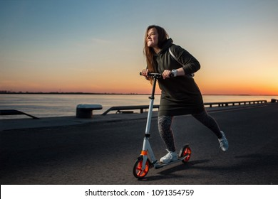 Joyful woman quickly riding a kick scooter on sunset