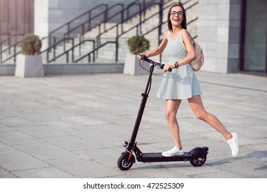 Joyful woman riding a kick scooter