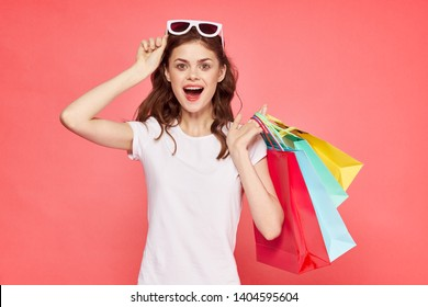 joyful woman with shopping bags over pink background