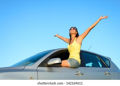 Joyful woman sitting on window new car raising arms up to the sky on summer trip. Blissful and fun happy girl on travel vacation.