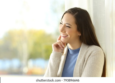 Joyful woman thinking looking at side through a window at home