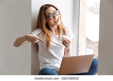 Joyful woman in t-shirt and eyeglasses sitting on windowsill with cup of coffee and laptop computer while looking at the camera and pointing at laptop