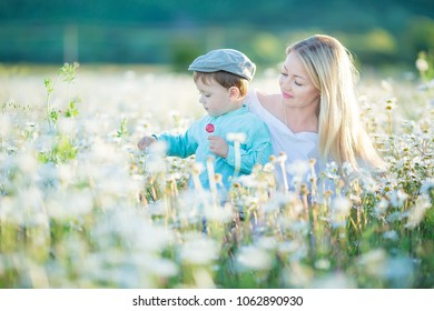 Joyful woman walk on green yellow flowering field background, rest, have fun, play, toss up little cute child baby boy. Mother, little kid son. Family day 15 of may, love, parents, children concept.