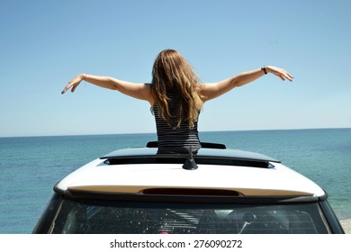 Joyful woman waving on summer car travel vacation to the coast. Brunette girl having fun leaning out vehicle sunroof towards the sea.