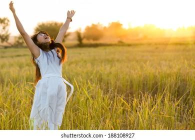 Joyful woman wearing white dress in a rice field after harvest, Thailand