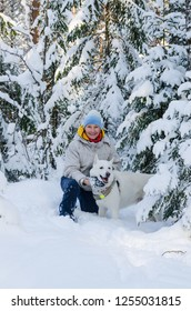 Joyful woman with a white dog in the winter snow-covered forest