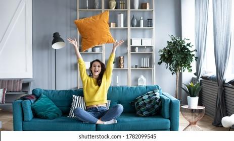 Fröhliche Frau in einem gelben Pullover und Jeans, die auf einem gemütlichen Sofa sitzen, werfen ein Kissen hoch ins Wohnzimmer zu Hause. Genießen Sie das häusliche Leben.