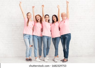 Joyful Women In Breast Cancer Pink T-Shirts With Ribbons Raising Hands Standing Together Over White Brick Wall. Oncology And Support