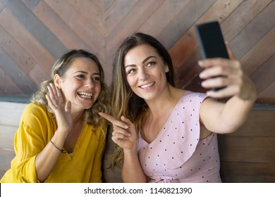 Joyful women using phone for video calling to mutual friend. Cheerful woman introducing her friend to subscribers when making video on smartphone. Communication concept