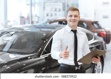 Joyful worker. Professional car salesman smiling joyfully showing thumbs up holding a clipboard working at the car dealership copyspace profession professionalism occupation career success businessman