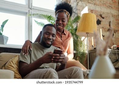 Jeune couple de jeunes Africains en vêtements de banals regardant l'écran de leur smartphone tenu par un homme souriant
