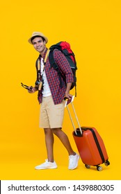 Joyful young Asian man with luggage being ready to travel on his vacation isloated on yellow studio background