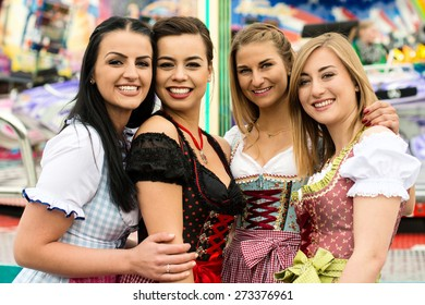 Joyful young and attractive women at German funfair Oktoberfest with traditional dirndl dresses and joyride in the background. Mixed nationalities, 2 girls rather typical German, one with Asian and