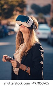 Joyful young beautiful girl gesture testing virtual reality 3D video glasses VR headset dressed in a office outfit impressed by augmented reality on the street and beautiful autumn sun light colors