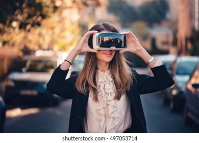 joyful young beautiful girl testing virtual reality 3D video glasses VR headset dressed in a office outfit impressed by augmented reality on the street with beautiful autumn sun light colors