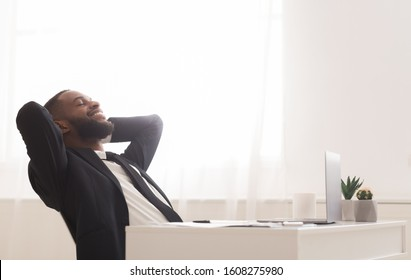 Joyful young black manager relaxing on chair in white modern office, leaning back with closed eyes, copy space