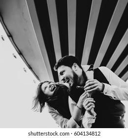 Joyful young couple hugs under the bridge