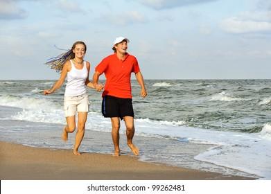 Joyful young couple running on sea shore.