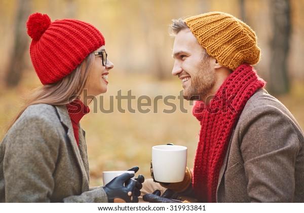 Joyful young couple talking outdoors while having tea