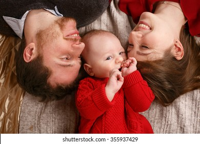 Joyful young family with a baby lying on the bed and smiling happily. The joy of parenthood.