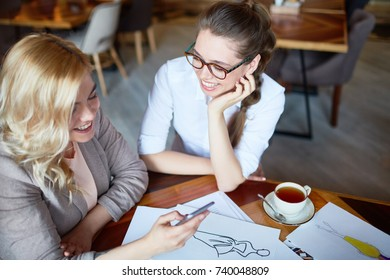 Joyful young fashion designers having fun while discussing joint project at cozy small coffeehouse, pretty blond-haired woman using smartphone