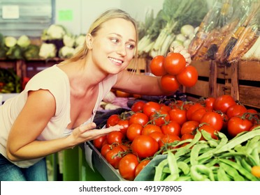 joyful young female customer choosing fresh ripe tomatoes on market