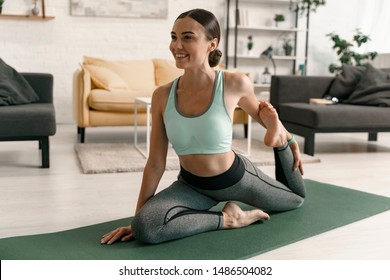 Joyful young female is doing stretching exercises on mat in living-room