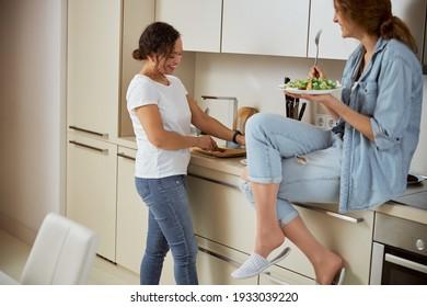Freudenjunge Weibchen, die sich beim Kochen lächeln lassen