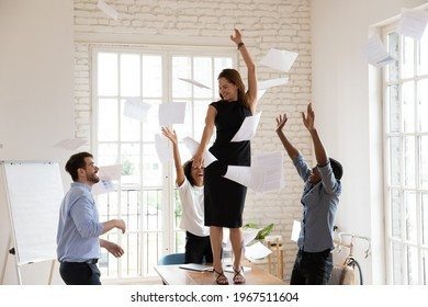 Joyful young female team leader boss dancing on table, having fun with diverse multiracial colleagues in modern office. Happy laughing mixed race employees throwing papers in air, celebrating success.