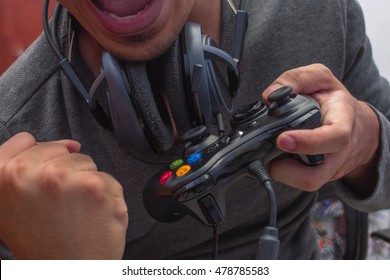 Joyful young gamer playing games using his controller.
