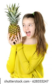 Joyful young girl holding a large pineapple on a white background.