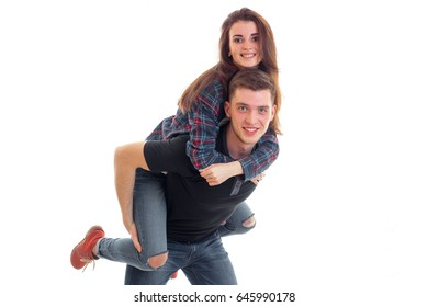 joyful young girl on shoulders by the beautiful fun guy