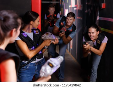 Joyful young girls took aim with colored laser guns during laser tag game in labyrinth