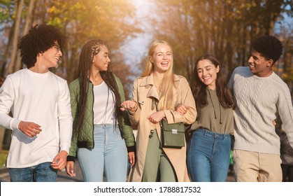 Joyful young international friends walking by public park, talking and laughing, teenagers spending time together