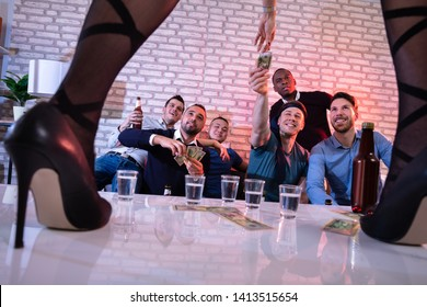 Joyful Young Male Friend Offering Money To Stripper Performing On Stage