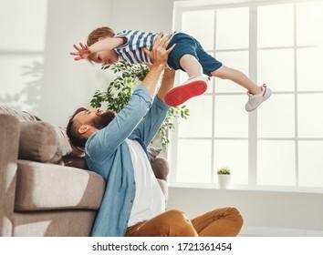 Freudender junger Mann in zwangloser Kleidung sitzend auf dem Boden und wirft glücklichen kleinen Sohn auf, während er sich im gemütlichen Wohnzimmer zu Hause amüsiert